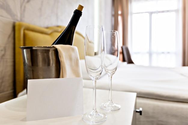 Concept de lune de miel. seau à champagne près du lit dans une chambre d'hôtel Photo Premium