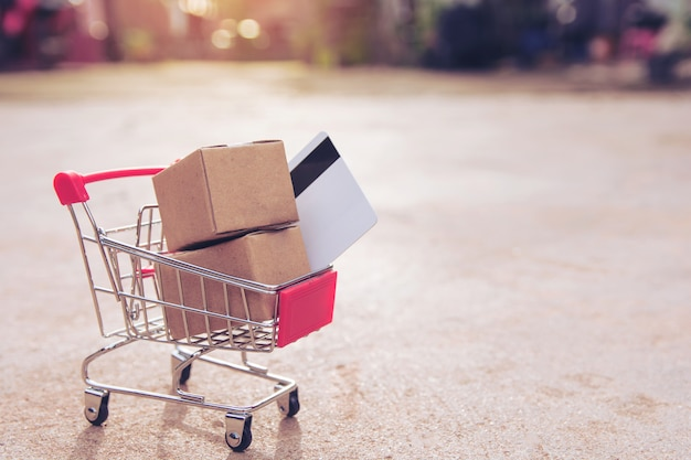 Concept de magasinage en ligne: boîtes de carton ou de papier et carte de crédit dans le panier. en ligne Photo Premium