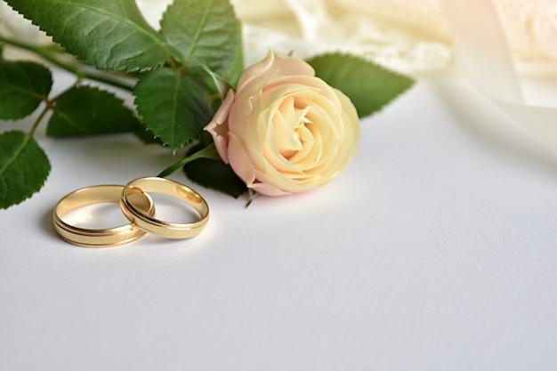 Concept de mariage, deux anneaux d'or, robe rose et blanche. Photo Premium