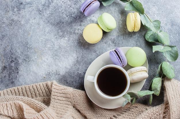 Concept de matin confortable. macarons pastel colorés délicieux avec crème et café, pull gris chaud Photo Premium