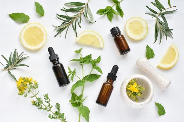 Concept de médecine alternative, cosmétiques naturels, herbes, citron, huiles, mortier et pilon, pose à plat. Photo Premium