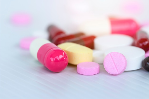 Concept de médecine; beaucoup de médicaments colorés. pilules et capsules sur fond blanc Photo Premium