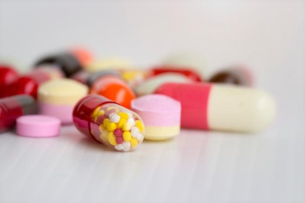 Concept de médecine; fermé l'image de médicaments colorés, capsules, pilules avec un fond blanc. Photo Premium