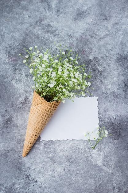 Concept minimal de printemps. cornet gaufré à fleurs de gypsophile. concept de jour de femme de mère. Photo Premium