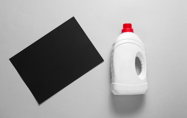 Concept Minimaliste De Lavage. Feuille De Papier Noir Pour L'espace De Copie, Bouteille De Gel Lavant Sur Table Grise. Vue De Dessus Photo Premium