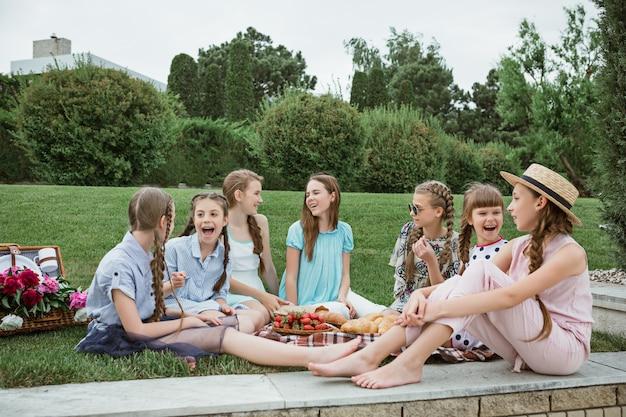 Concept De Mode Pour Enfants. Le Groupe D'adolescentes Assis à L'herbe Verte Au Parc Photo gratuit