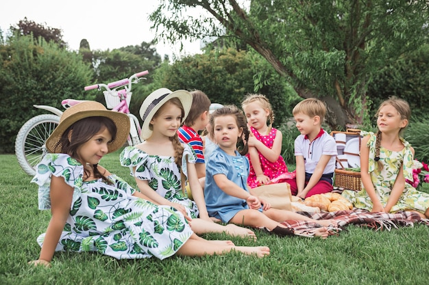 Concept De Mode Pour Enfants. Le Groupe D'adolescents Garçons Et Filles Assis à L'herbe Verte Au Parc. Photo gratuit