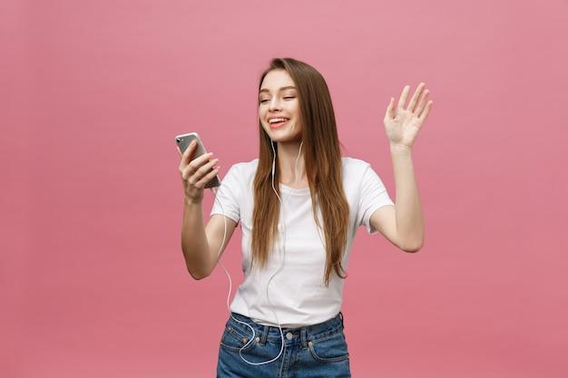 Concept de mode de vie. jeune femme à l'aide de téléphone pour écouter de la musique sur fond rose Photo Premium