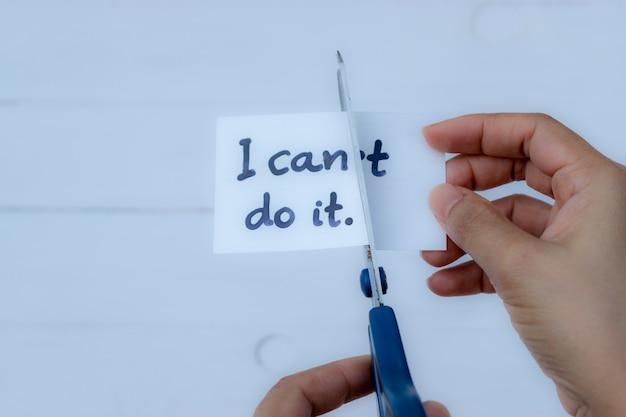 Concept de motivation, mains de femme tenant une carte je peux le faire avec des ciseaux. Photo Premium