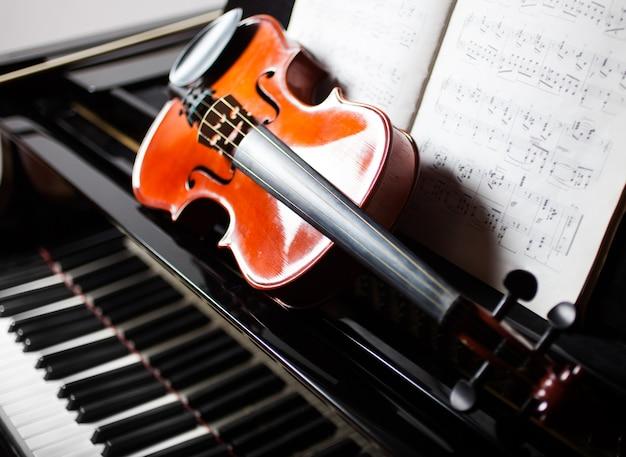 Concept de musique classique: violon et partition sur un piano Photo Premium