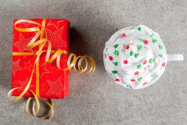 Concept De Noël Et Du Nouvel An Une Boîte-cadeau De Noël En Papier Rouge Et Tasse De Café Ou De Chocolat Chaud Avec De La Crème Fouettée Et Une Décoration D'étoiles Douces Sur Une Table En Pierre Grise Photo Premium