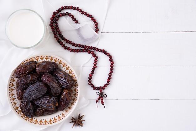 Concept de nourriture et de boissons du ramadan. chapelet en bois, lait et fruits de dattes Photo Premium