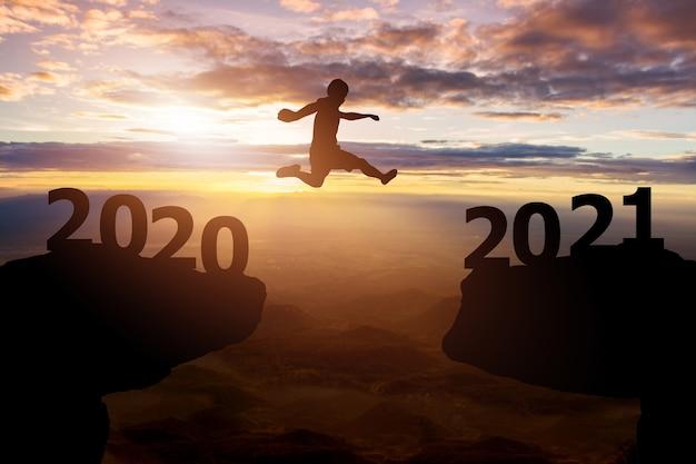 Concept De Nouvel An Succès 2021.silhouette Homme Saute Entre 2020 Avec Collines Et Fond De Coucher De Soleil Ciel Photo Premium