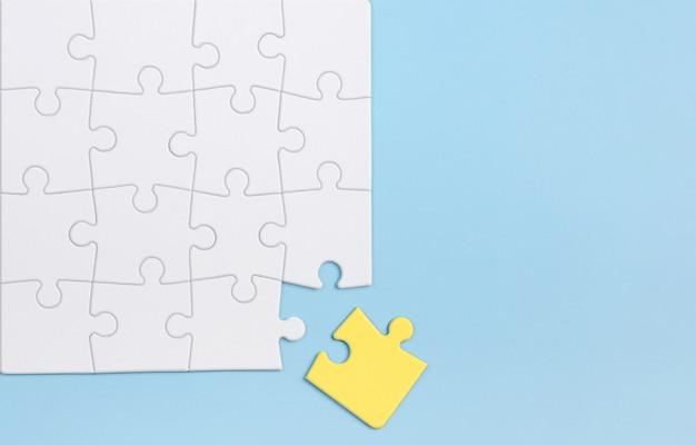 Concept De Pensée Et D'individualité Hors De La Boîte. Puzzle Jaune Contre Les Blancs Sur Le Mur Bleu. Photo Premium