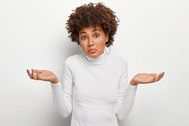 Concept De Perception De Personnes, D'attitude Et De Vie. Femme Ignorante Et Ignorante Aux Cheveux Bouclés, écarte Les Paumes Dans Le Doute Photo gratuit