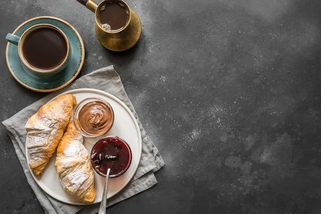 Concept petit déjeuner français avec café noir et croissant. vue de dessus. copier l'espace pour le texte. Photo Premium