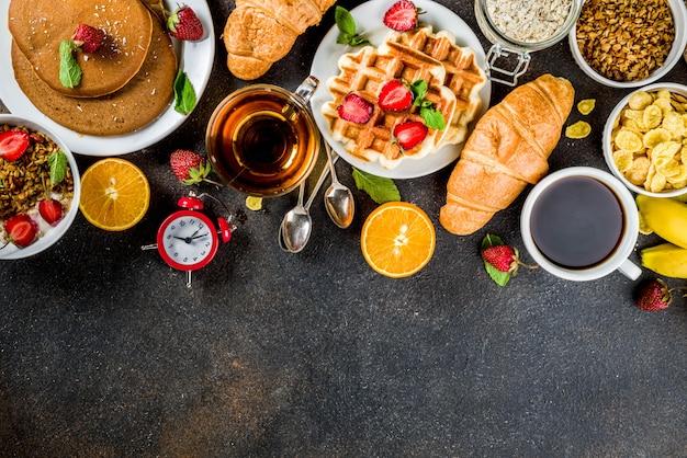 Concept de petit-déjeuner sain, divers plats du matin - crêpes, gaufres, sandwich à l'avoine et aux céréales avec yaourt, fruits, baies, café, thé, fond de jus d'orange Photo Premium