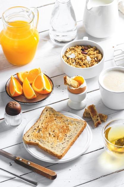 Concept De Petit-déjeuner Sain, Divers Plats Du Matin - Crêpes, œuf à La Coque, Toast, Flocons D'avoine, Muesli, Fruits, Café, Thé, Jus D'orange, Lait Sur Une Table En Bois Blanche Photo Premium