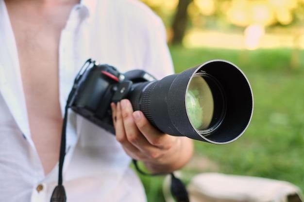 Concept de photographie ou de voyageur. le photographe tient la caméra dsrl dans ses mains Photo Premium