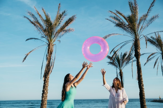 Concept de plage et d'été avec des femmes joyeuses et des palmiers Photo gratuit