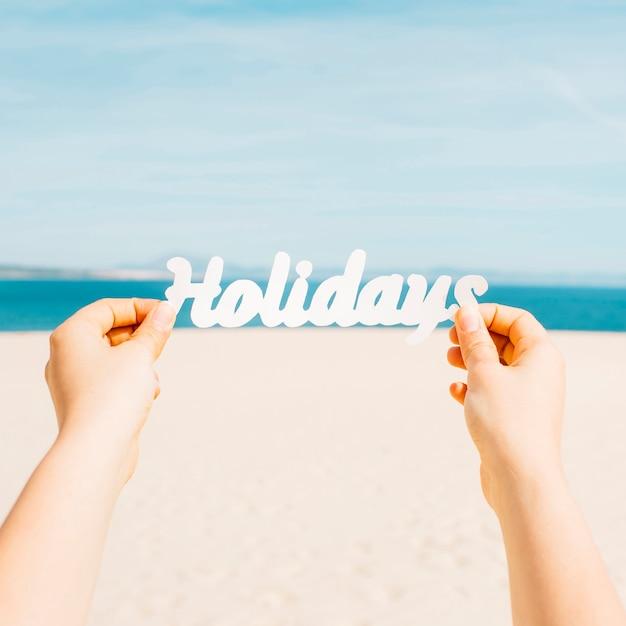 Concept de plage avec des mains tenant des lettres de vacances Photo gratuit
