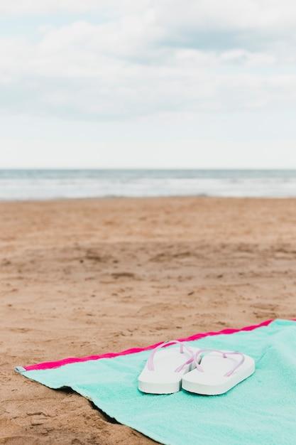 Concept de plage avec des tongs sur une serviette Photo gratuit