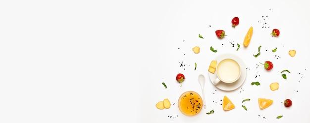 Concept plat de pose d'une tasse de thé au gingembre, de cubes de sucre, de fraises, de morceaux de gingembre, de feuilles d'orange et de menthe Photo Premium