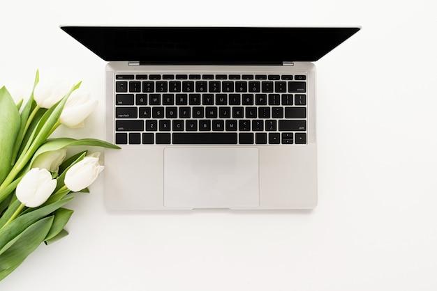 Concept De Printemps. Vue De Dessus De La Maquette D'un Ordinateur Portable, Fleurs De Tulipes Blanches Photo Premium