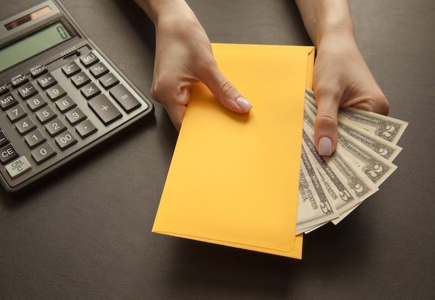 Concept de recevoir un salaire dans une enveloppe. enveloppe jaune avec de l'argent sur une table sombre. Photo Premium