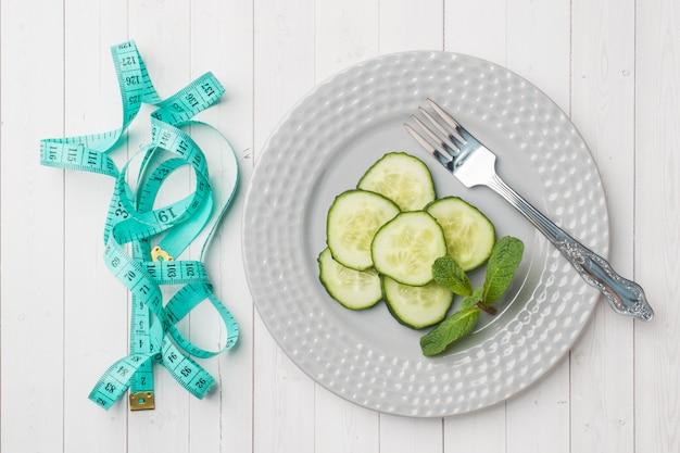 Concept de régime. diapositives de concombre frais sur une assiette et ruban adhésif centimètre sur une table blanche. Photo Premium