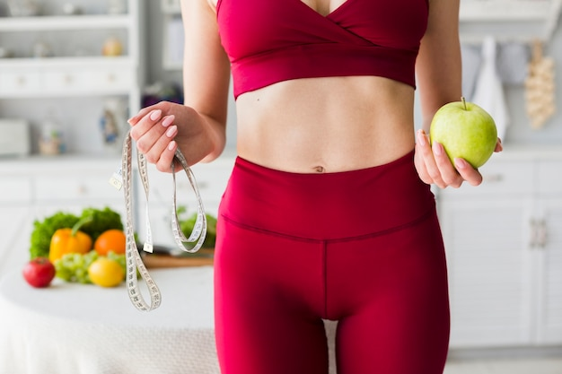 Concept de régime avec femme sportive en cuisine Photo gratuit