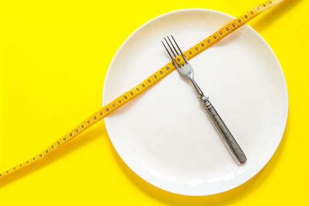 Concept de régime. fourchette sur une assiette blanche avec centimètre. Photo Premium