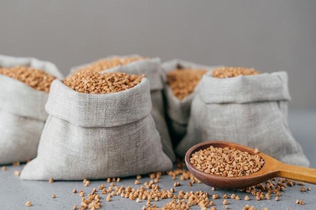Concept de régime et de nutrition. sarrasin brun récolté dans des sacs, isolé sur fond gris. céréales sèches prêtes à cuire Photo Premium