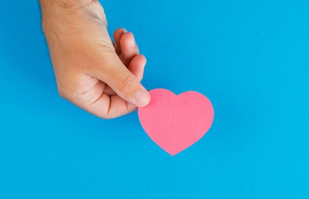 Concept De Relation Sur Table Bleue à Plat. Main Tenant Le Coeur En Papier Découpé. Photo gratuit