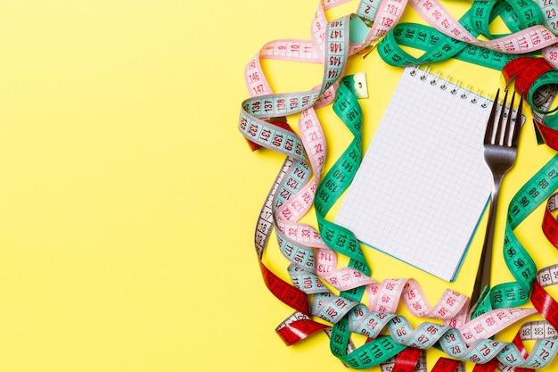Concept de remise en forme avec un espace vide pour votre design sur fond jaune. vue de dessus du bloc-notes et une fourchette entourée de rubans à mesurer colorés Photo Premium