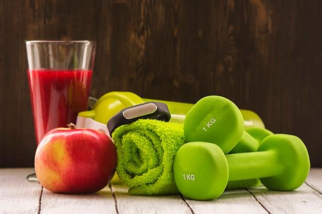 Concept de remise en forme ou de régime alimentaire: haltères, smoothie rouge frais, pomme Photo Premium