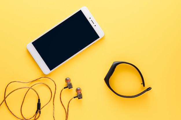 Concept de remise en forme avec téléphone portable, écouteurs et tracker de remise en forme sur fond jaune Photo Premium