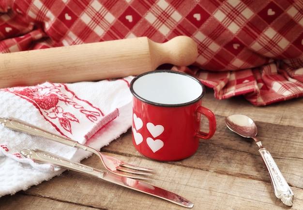 Concept de saint-valentin avec coeurs décorés mug et ustensiles de cuisine Photo Premium