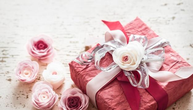 Concept De La Saint-valentin Et De La Fête Des Mères, Coffret Rouge Avec Noeud Et Roses Sur Fond De Bois Clair Photo gratuit
