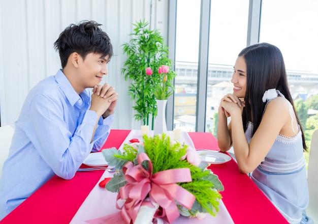 Concept De La Saint-valentin, Heureux Jeune Couple Asiatique Doux Ayant Romantique Le Déjeuner Avec Un Bouquet De Roses Au Restaurant Photo Premium