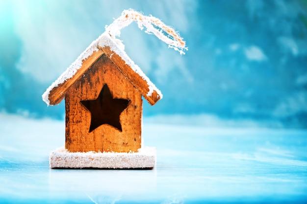 Concept Saisonnier Et Vacances. Jouet De Maison Décorative Sur Un Fond D'hiver De Glace Bleue. Mise Au Point Sélective Photo Premium