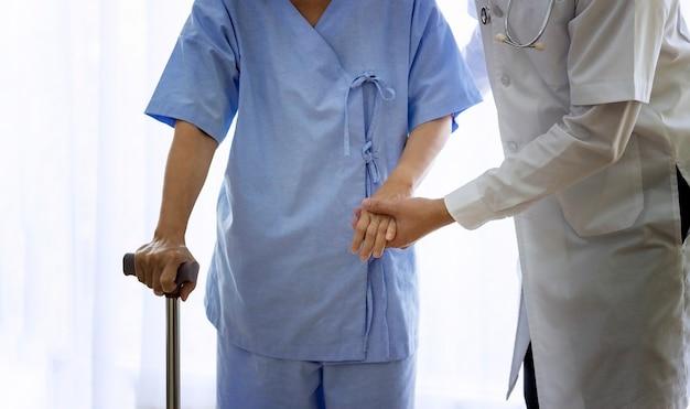 Concept de soins aux patients âgés; asiatique médecin soutenant une patiente âgée en utilisant walker à l'hôpital. Photo Premium