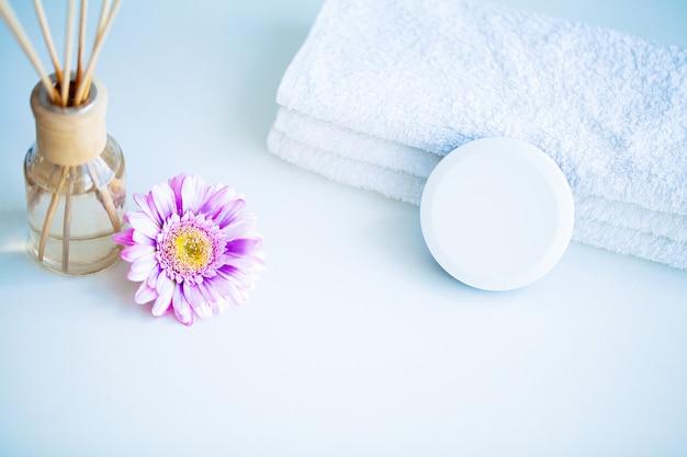 Concept spa. crème hydratante, serviettes et huile aromatique sur la table dans la salle de bain Photo Premium