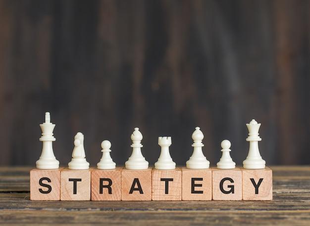 Concept De Stratégie D'entreprise Avec Des Pièces D'échecs Sur Des Cubes En Bois Sur La Vue De Côté De Table En Bois. Photo gratuit