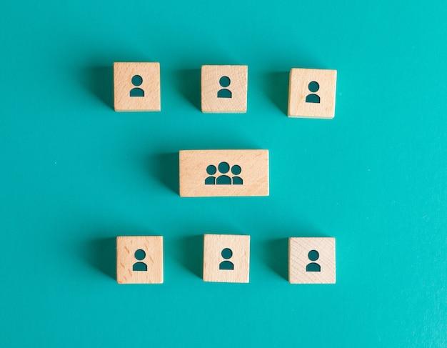 Concept De Structure De Gestion Avec Des Icônes De Personnes Sur Des Blocs De Bois Sur Une Table Turquoise à Plat. Photo gratuit