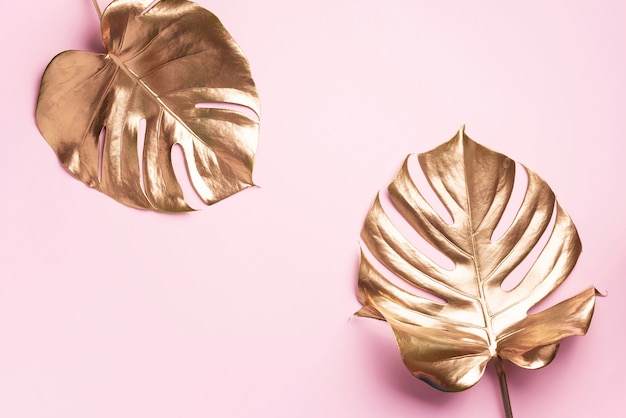 Concept de style minimal floral. tendance estivale exotique. feuille de monstera de palmier tropical doré Photo Premium
