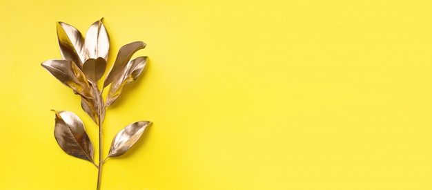 Concept de style minimal floral. tendance estivale exotique. feuilles tropicales dorées et branche Photo Premium