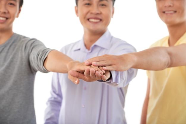 Concept de teambuilding, trois hommes recadrés s'empilant les mains Photo gratuit