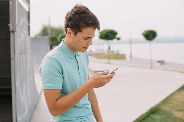 Concept de technologie, internet et personnes - adolescent heureux avec smartphone à l'extérieur. Photo Premium