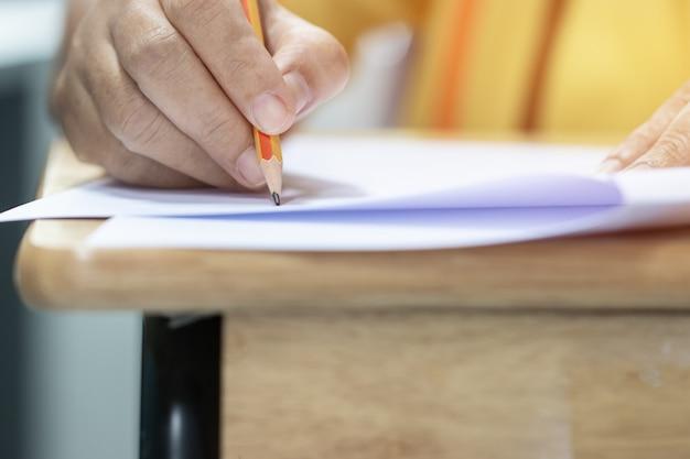 Concept de test d'éducation: lycée de l'homme, étudiant tenant un crayon pour les tests Photo Premium